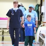 Dr Pinheiro walking with a kid into